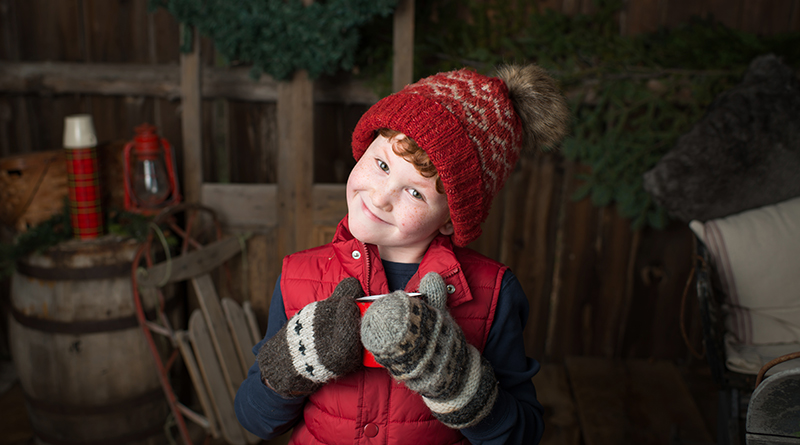 Little boy with hat and glove and hot chocolate