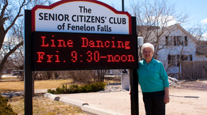 Senior standing by club sign