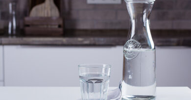 Glass of pure water and bottle on kitchen table.
