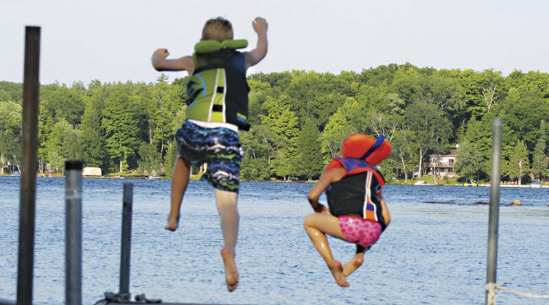 two kids jumping into the water