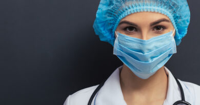 Beautiful young doctor in white medical gown.