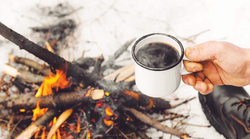 Male hands hold a mug of coffee near a burning campfire. Concept hike, walk, trip in winter
